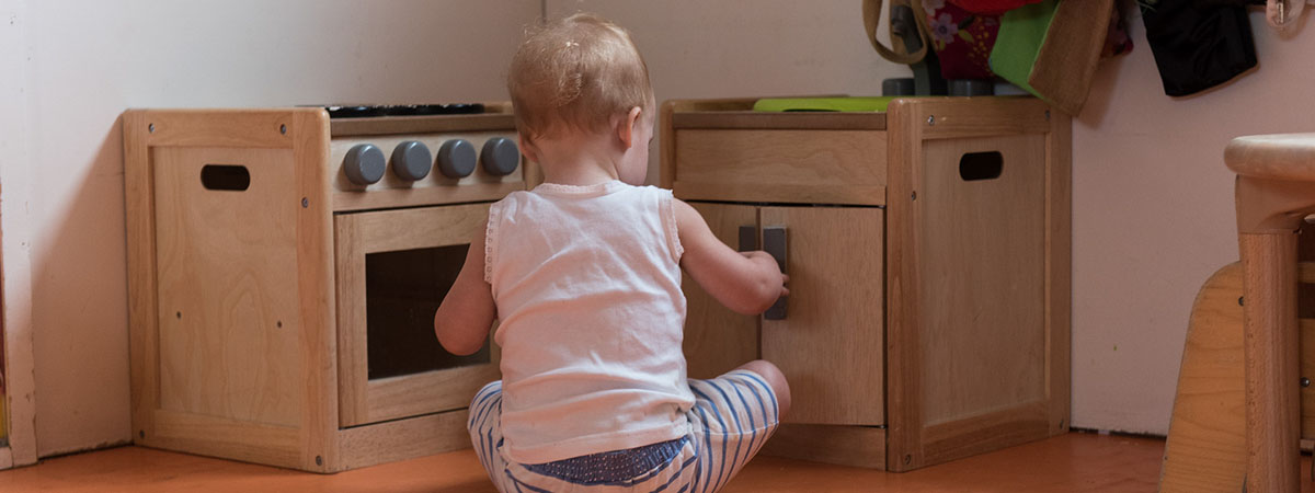 toddler sat in front of cupboards