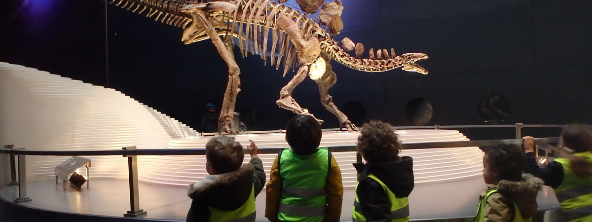 young children visitng a dinosaur in a museum with minihome nursery