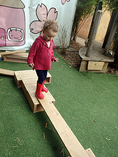 toddler at mini home nursery on a plank